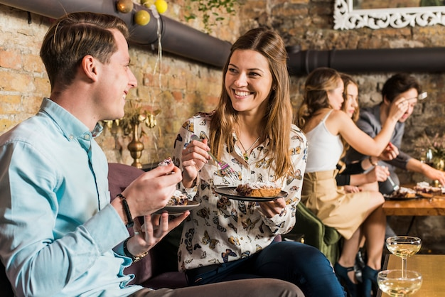 Happy couple eating pizza slice on plate Free Photo
