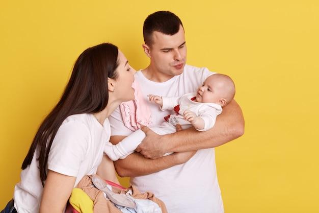 Счастливая пара, обнимая и глядя на новорожденного ребенка на желтом фоне, разговаривая с маленькой дочкой с любовью и улыбкой, родители в белых футболках, счастливая семья в помещении. Бесплатные Фотографии