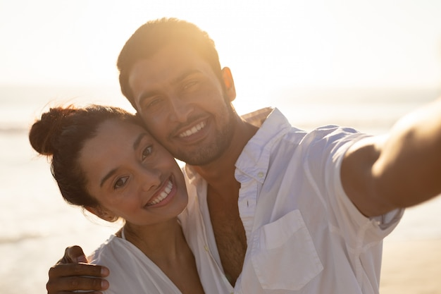 Happy couple embracing each other on the beach 4k Free Photo