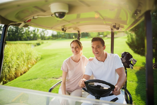 Happy couple family is driving golf car on course. Premium Photo