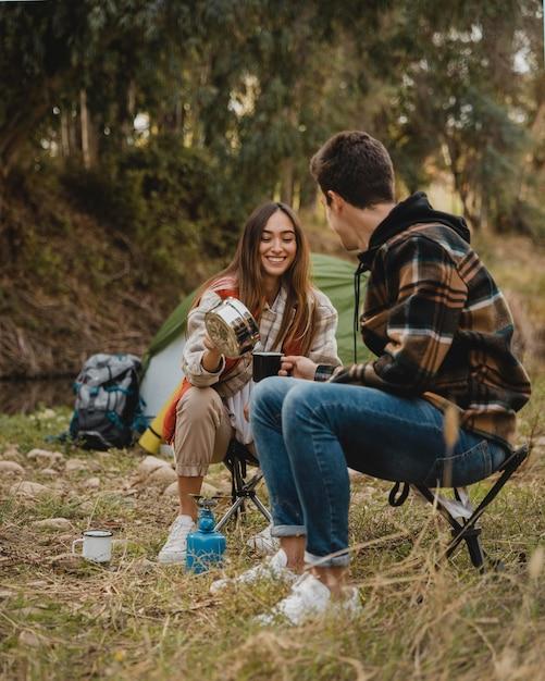 Coppie felici nella foresta che stanno insieme al campeggio Foto Gratuite