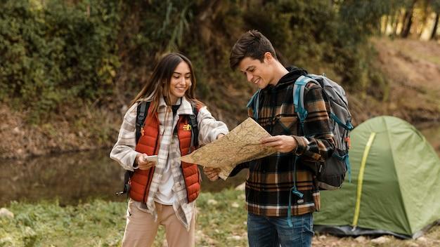 Coppie felici nella foresta che guardano insieme sulla vista frontale della mappa Foto Gratuite