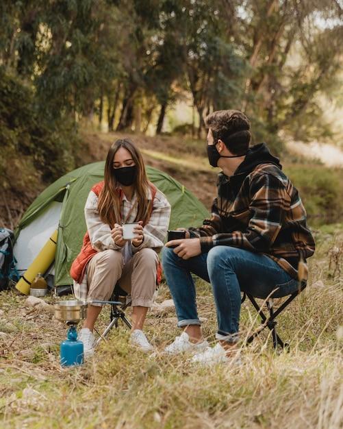 Coppia felice nella foresta indossando maschere mediche Foto Gratuite