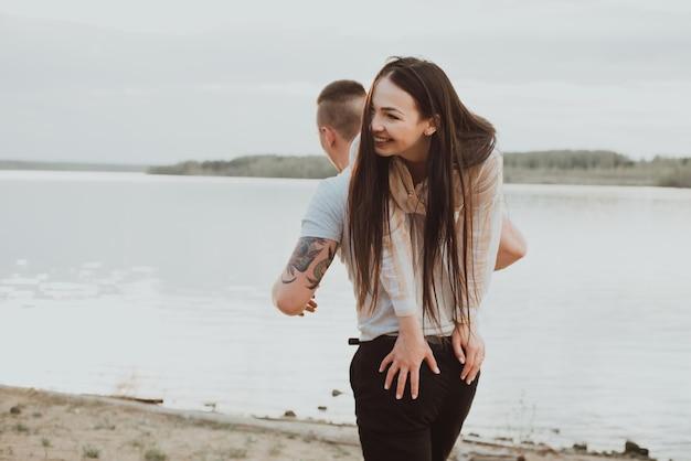 幸せなカップルの女の子と夏の川沿いのビーチで楽しんでいる男 Premium写真