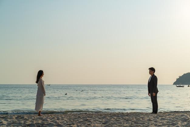 夏の熱帯の砂浜に新婚旅行に行く幸せなカップル Premium写真