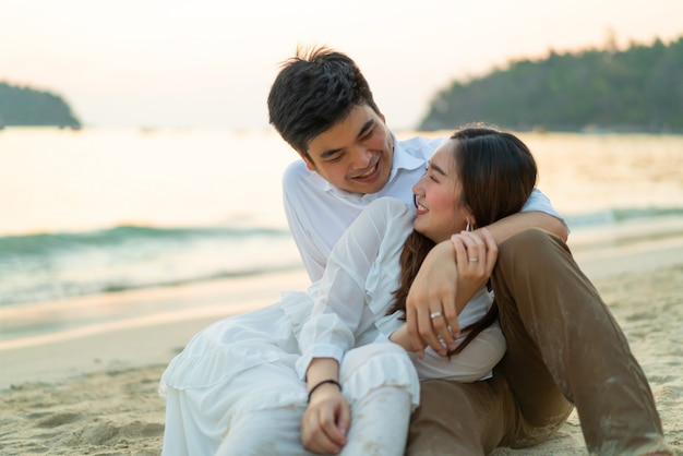 Happy couple going honeymoon travel on tropical sand beach in summer Premium Photo