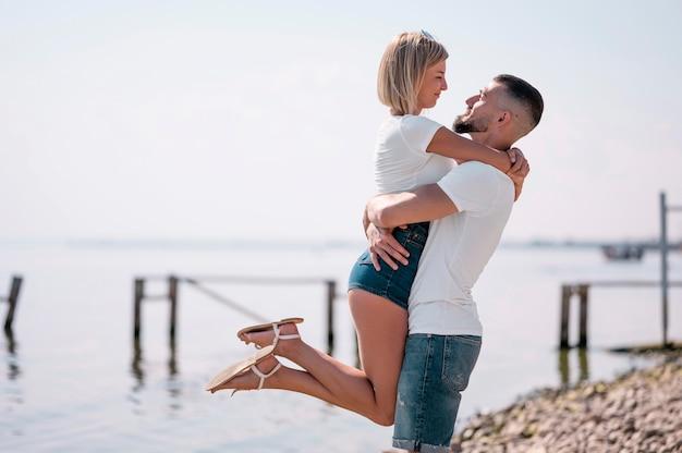 Coppie felici che vanno in giro insieme sulla spiaggia Foto Gratuite