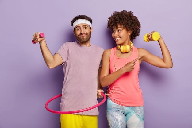 幸せなカップルはスポーツのようにトレーニングを受けています、無精ひげを生やした男は小さなダンベルを持っています、フラフープでエクササイズ、満足している暗い肌の女の子は上腕二頭筋を示し、体重でトレーニングし、ヘッドフォンで音楽を聴きます 無料写真