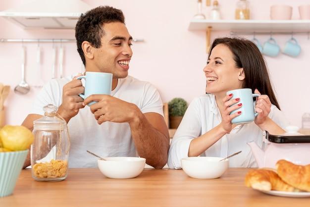Happy couple having breakfast in the kitchen Free Photo