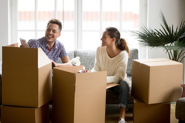 Happy couple having fun laughing unpacking boxes on moving day Free Photo