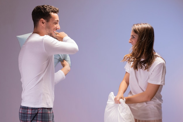 Happy couple having a pillow fight Free Photo