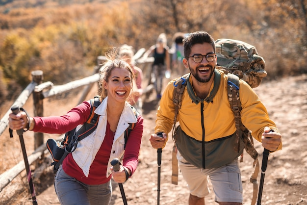 Happy couple hiking in the autumn. in background rest of the group. Premium Photo