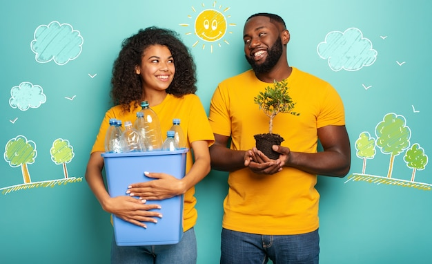 Happy couple hold a plastic container with bottles and a small tree over a light blue color concept of ecology conservation recycling and sustainability Premium Photo