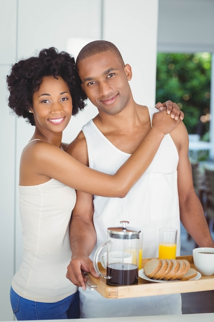 Happy couple holding breakfast tray in the kitchen at home Premium Photo