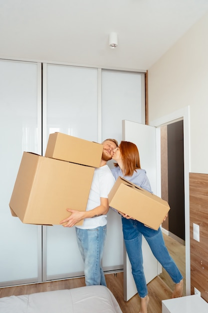 Happy couple holding cardboard boxes and moving to new place Free Photo