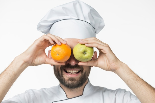 Happy couple holding ripe fruits in front of his eye against white background Free Photo