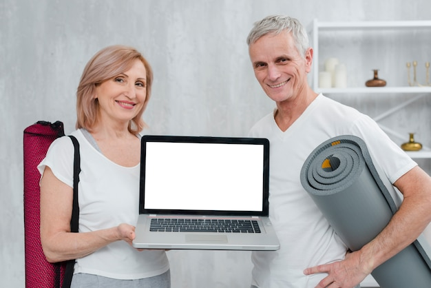 Happy couple holding yoga mat and laptop with white screen at home Free Photo