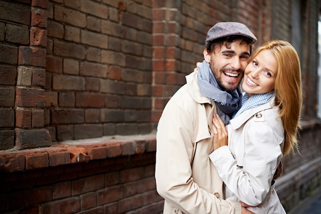 Happy couple hugging each other on the street Free Photo