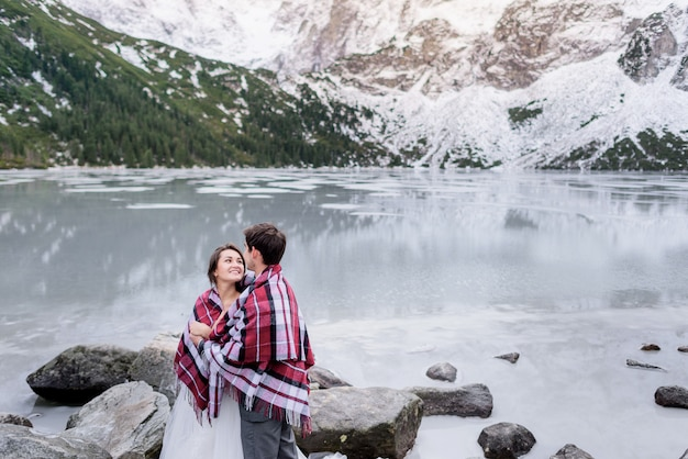 Счастливая влюбленная пара смотрит друг на друга перед захватывающими дух зимними горными пейзажами и замерзшим озером татры Бесплатные Фотографии