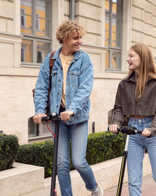 Счастливая пара в городе на электрических скутерах Premium Фотографии