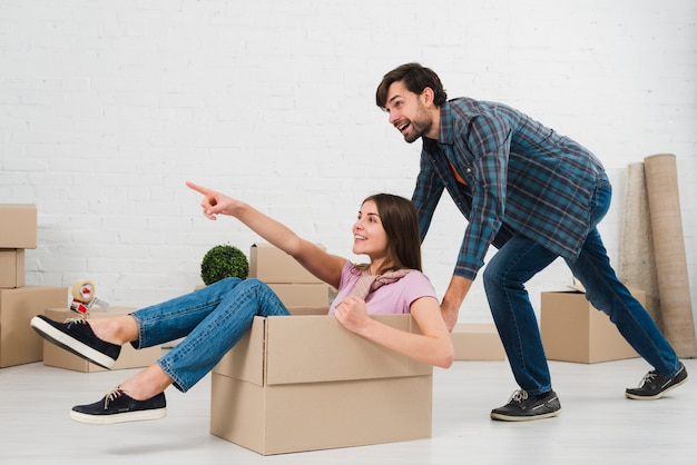 Happy couple is having fun with cardboard boxes in new house Free Photo