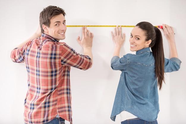 Happy couple is measuring their new empty apartment. Premium Photo