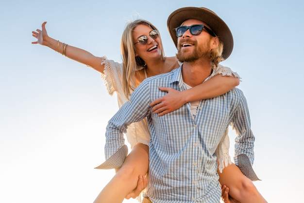 Happy couple laughing traveling in summer by sea, man and woman wearing sunglasses Free Photo