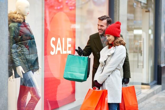 Coppia felice guardando il display del grande negozio Foto Gratuite