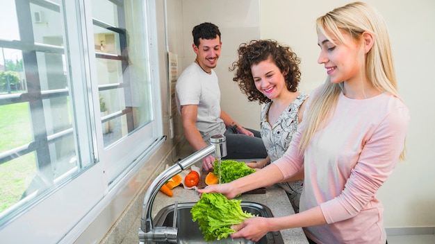 Happy couple looking at young female friend washing the lettuce in the kitchen sink Free Photo