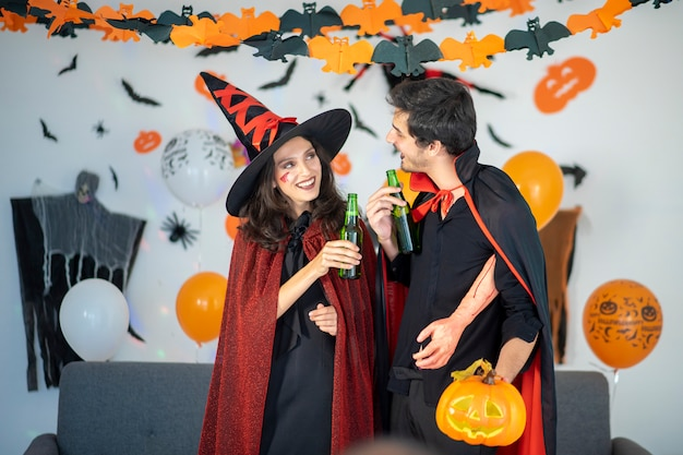 Happy couple of love  in costumes and makeup on a celebration of halloween Premium Photo