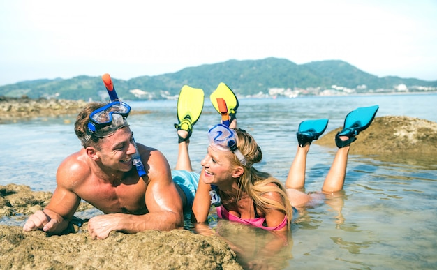 Happy couple in love having fun at tropical beach in thailand with snorkel mask and fins Premium Photo