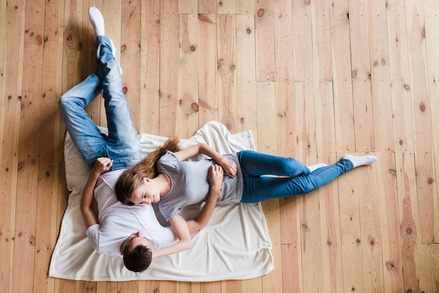 Happy couple lying on sheet on floor Free Photo