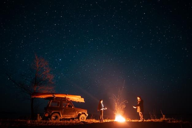 행복 한 커플 남자와여자가 타는 모닥불 앞에 서 무료 사진