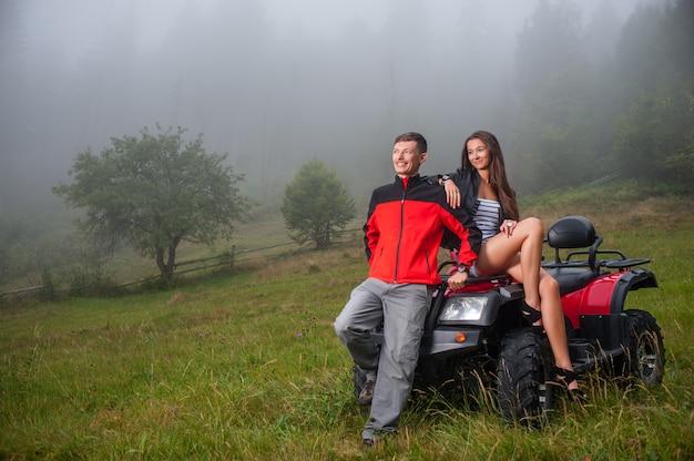Happy couple near four-wheeler atv in foggy nature Premium Photo