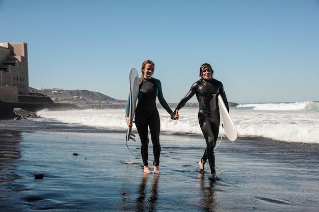 Счастливая пара серферов гуляет и смеется вдоль морского берега с черным песком в солнечный день Premium Фотографии