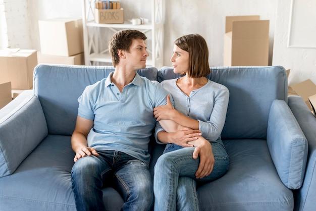 Счастливая пара на диване, собирая вещи, чтобы переехать Бесплатные Фотографии