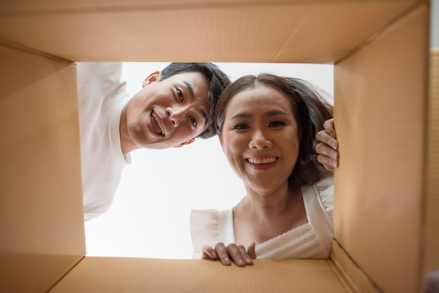 Happy couple opening a box and looking inside to product Free Photo