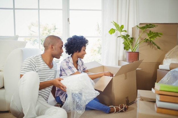 Happy couple opening boxes in the living room Premium Photo
