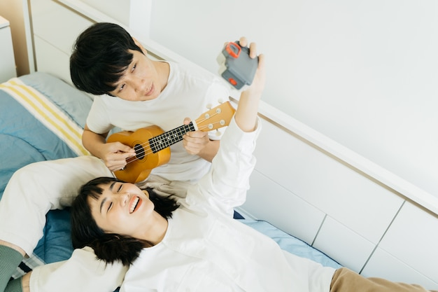 Happy couple playing ukulele and take a photo by themself Premium Photo