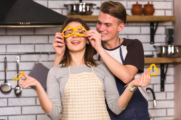 Happy couple playing with vegetables in kitchen Free Photo
