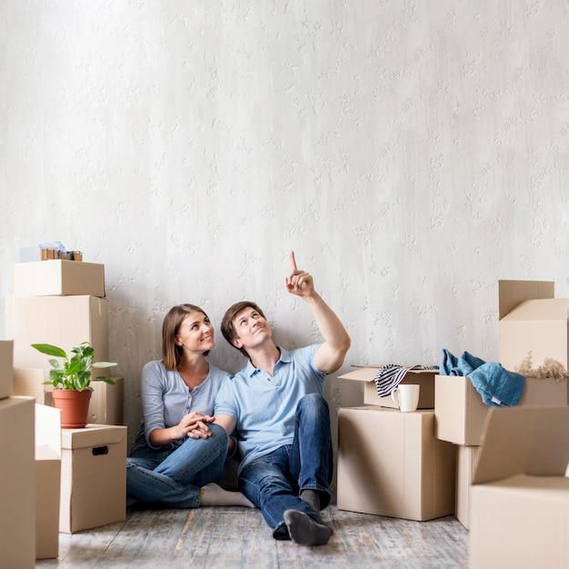 Счастливая пара, указывая вверх во время упаковки, чтобы съехать Premium Фотографии