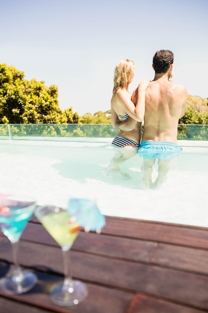 Happy couple in the pool with cocktails on the edge Premium Photo