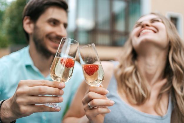 Счастливый портрет пары звон двух бокалов с игристым вином и клубникой внутри с размытым домом на фоне. празднование любви Бесплатные Фотографии