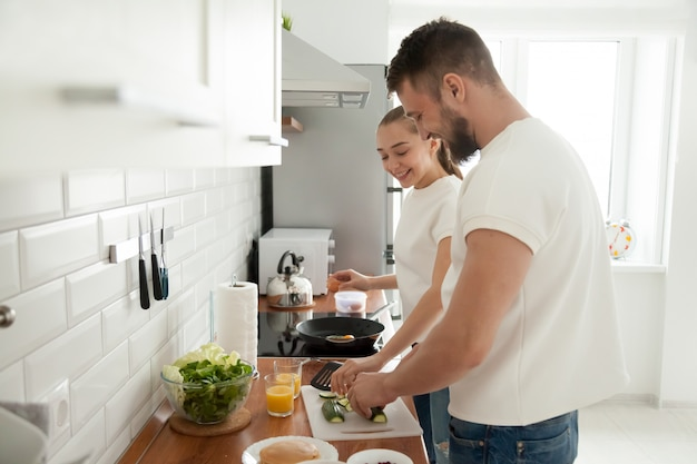 Happy couple preparing breakfast together in kitchen in morning Free Photo
