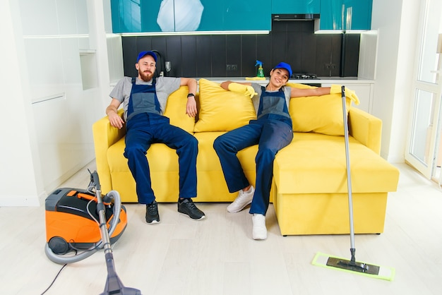 Happy couple of professional cleaners having rest in sofa after cleaning cuisine. Premium Photo