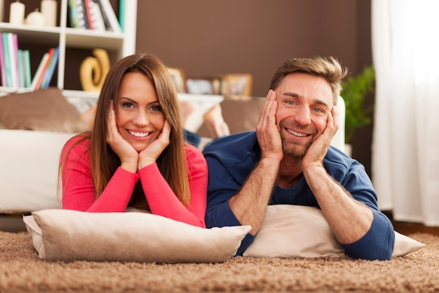 Coppie felici che si rilassano sul tappeto a casa Foto Gratuite