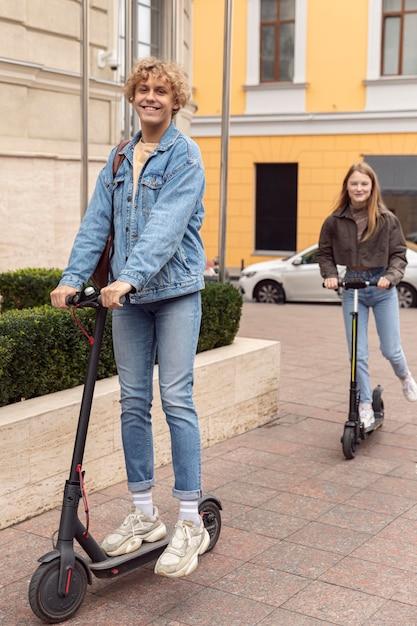 Счастливая пара на электрических скутерах в городе Premium Фотографии