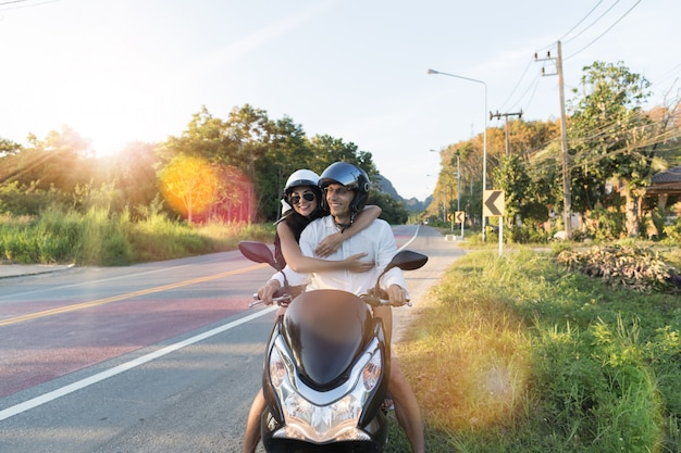 Happy couple riding motorcycle in countryside excited woman and man travel on motorbike road trip Premium Photo
