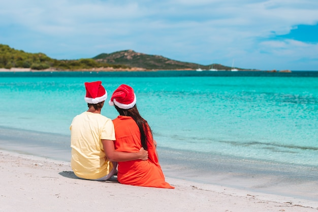 Happy couple in santa hats on the beach Premium Photo