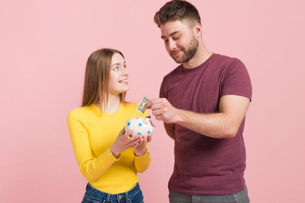 Happy couple saving money Free Photo